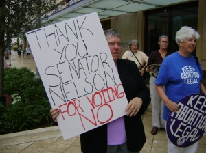 Florida NOW Pres. Donna Slutiak, holding sign, and past Florida NOW Pres. Clarice Pollock